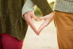 A couple making a heart with their hands
