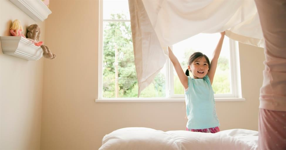 Young girl setting up her bedroom after she has moved