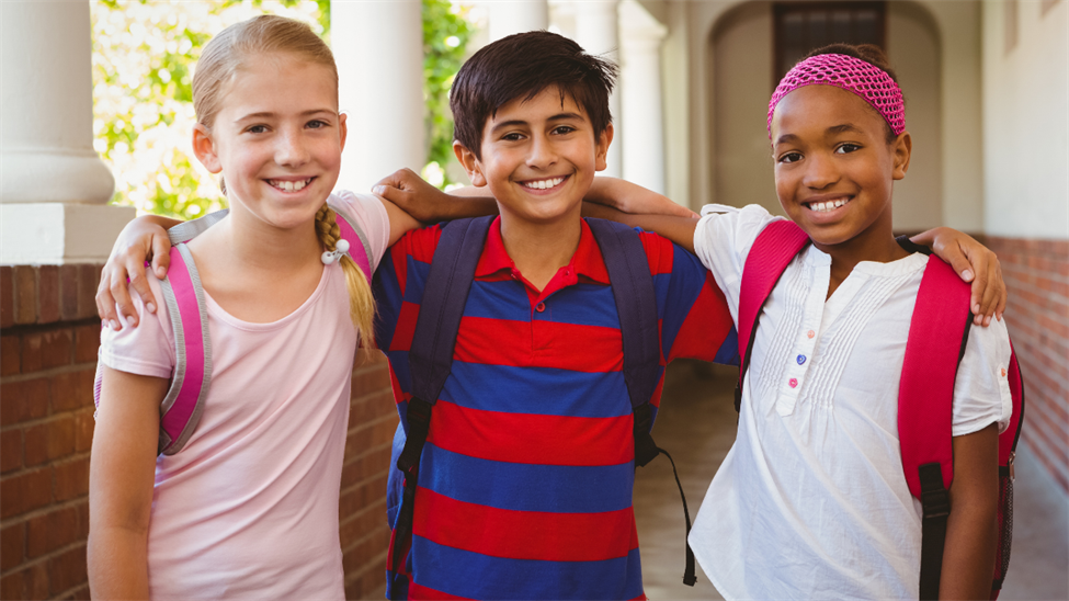 Three smiling children standing in front of school