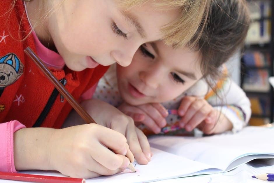 Two little girls writing in a school classroom