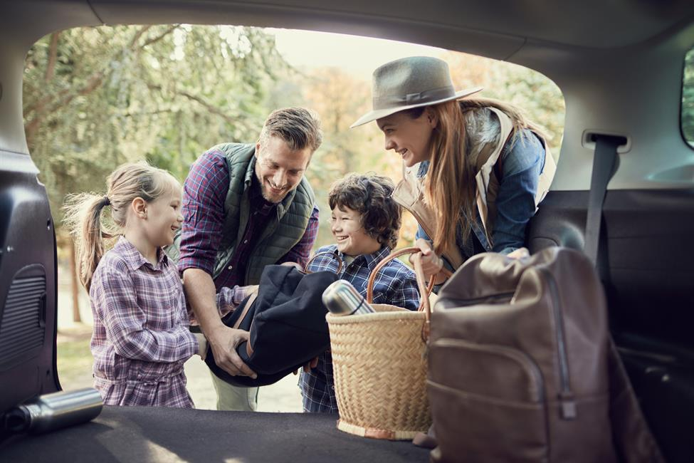 Family gathering their belongings in a car and getting ready for a cross-country vacation.
